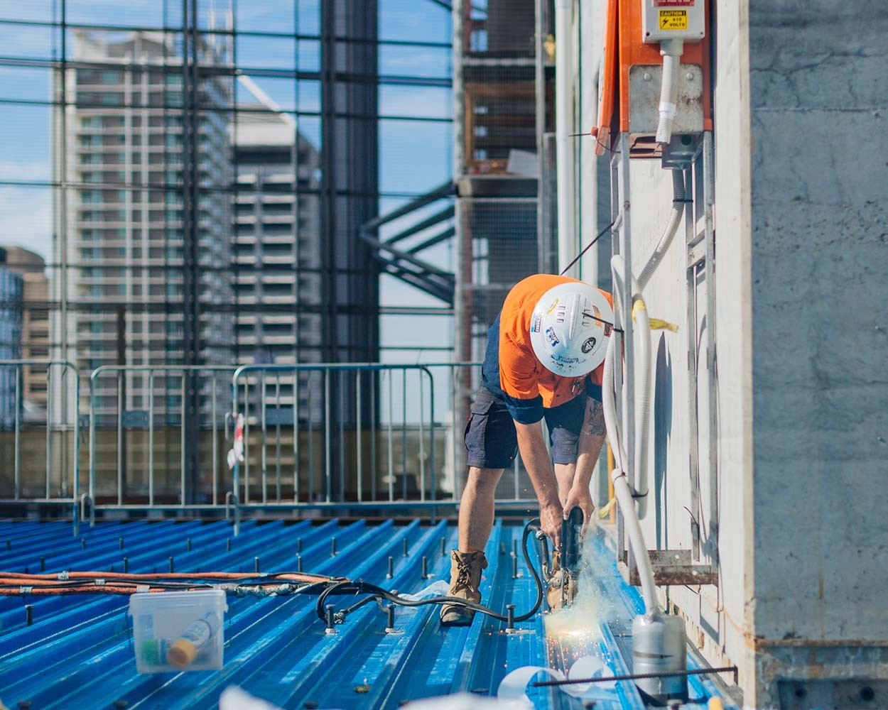 A construction worker on a roof drilling