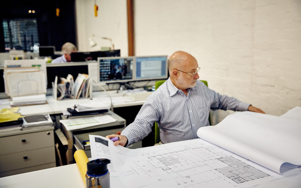 Man sitting at a desk working with architectural drawings